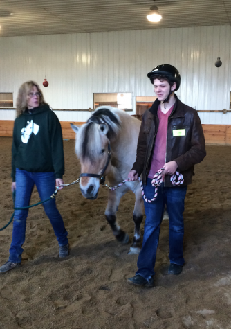 Junior Ross Reid-Anderson walks a horse at Equestrian Connection in Lake Forest for his Service Day project.