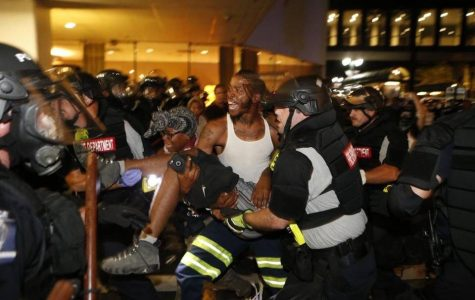 Officials help injured civilian during the riot in Charlotte, North Carolina