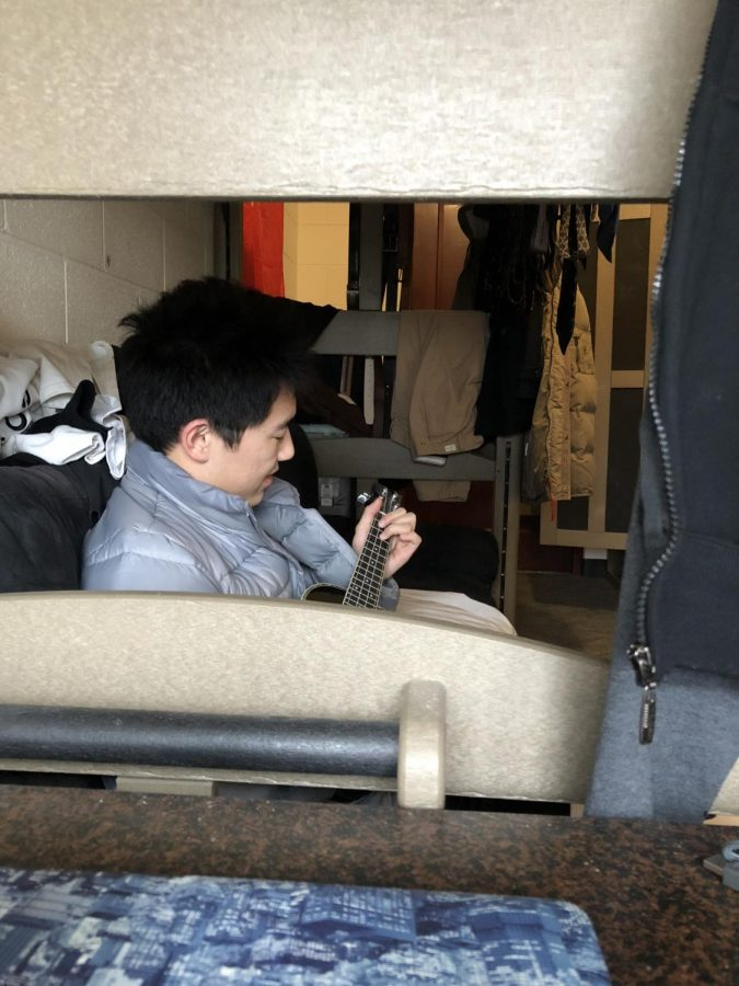 Clint Shi kills time in his Atlass dorm room by playing his ukulele.