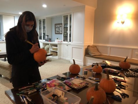 Regina Cummings '24 decorates a pumpkin during a social distanced dorm activity in Ferry Hall. Many dorm events had to altered or scrapped to fit social distancing guidelines. These new parameters have pushed dorm parents, proctors, and dorm councils to come up with new, creative activties.