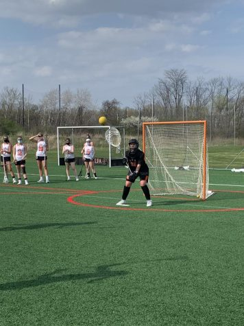Shayna Goldberg '22 saves a lacrosse shot during her first game as goalie.