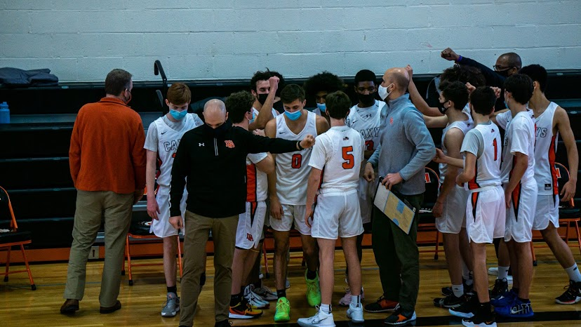 Members of the Boys' Varsity Basketball team participate in a masked huddle during the 2020-2021 season.
